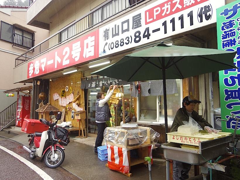 豆腐店から30分あまり、JR大歩危駅前にある小さな名物スーパー「歩危マート」さんに配達。すぐさま縄で結んだ豆腐がお店の前に。