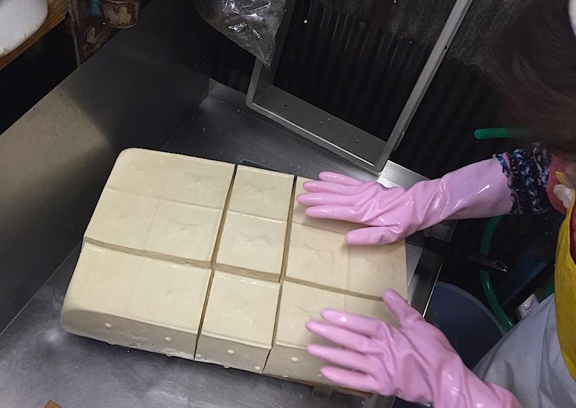 豆腐を圧搾させる水切り器で一度に作られる分量は15丁分、その重さは12kgにもなる。15丁箱と呼ばれる箱の大きさで作られた豆腐は、2丁分の大きさで7つと1丁(写真の真ん中下)という合計8片に断裁される。