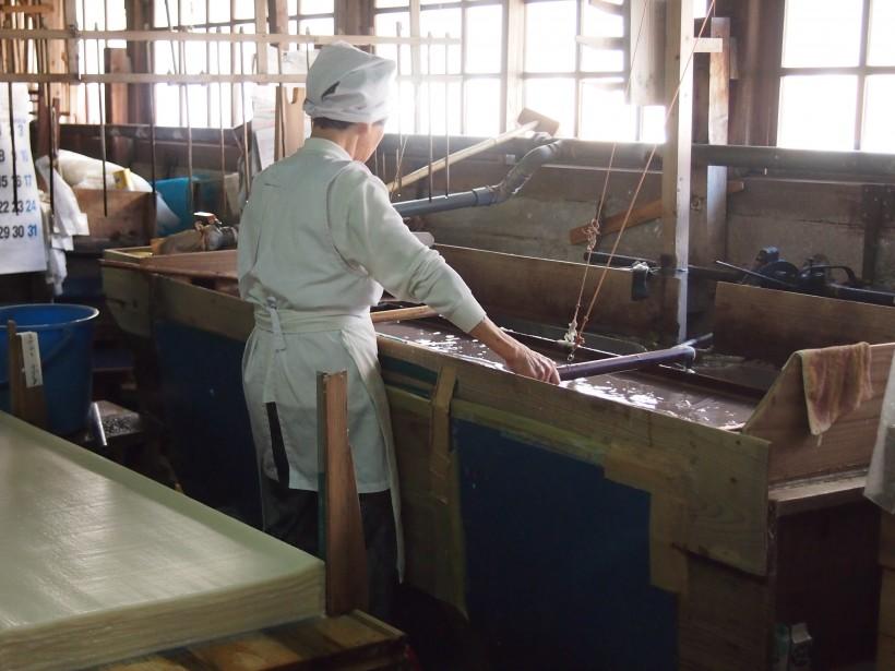 熟練の職人さん。大きな木枠を揺すって紙を漉きます。